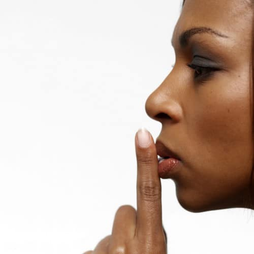 Young Businesswoman with Her Finger on Her Lips