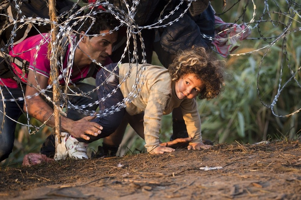 Refugees clamber through barbed wire as they cross from Serbia to Hungary, in Roszke, Thursday, Aug. 27, 2015. Over 10,000 migrants, including many women with babies and small children, have crossed into Serbia over the past few days and headed toward Hungary. (AP Photo/Darko Bandic)