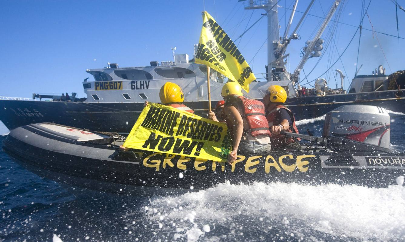 """Greenpeace activists demonstrate against tuna fishing operations in the international waters of the Pacific by deploying a banner reading """"Marine Reserves Now"""" alongside the Korean purse seiner Olympus"""