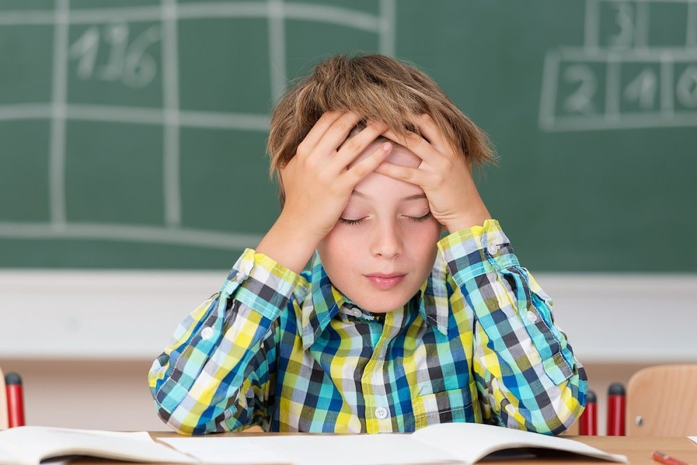 Young boy concentrating on his schoolwork sitting at his desk in the classroom with his head in his hands reading his class notes